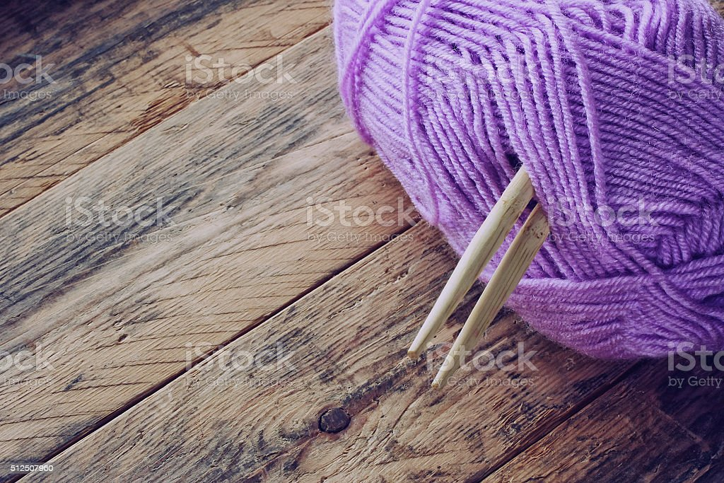 lilac skein of yarn, wooden knitting needles stock photo