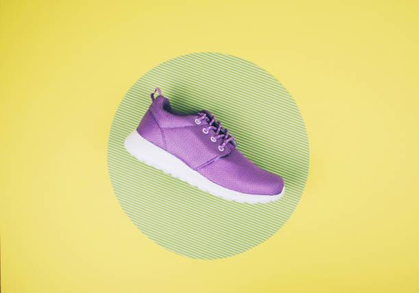 lila sneakers für eine multi-farbige pastell oberfläche. ansicht von oben, mode-stil. - neue sneaker stock-fotos und bilder