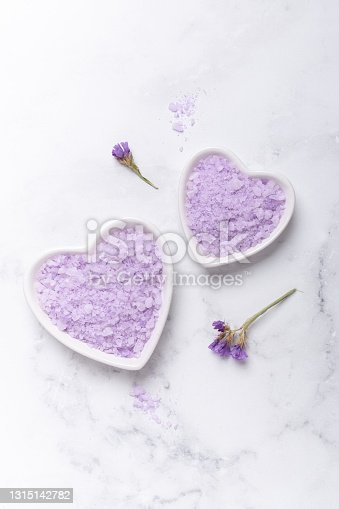 istock Lilac spa sea salt on marble background. Daily bodycare concept, natural bath products 1315142782