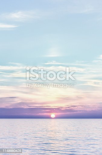 A soft lilac-hued sunset over a calm sea with the sun about to touch the horizon.