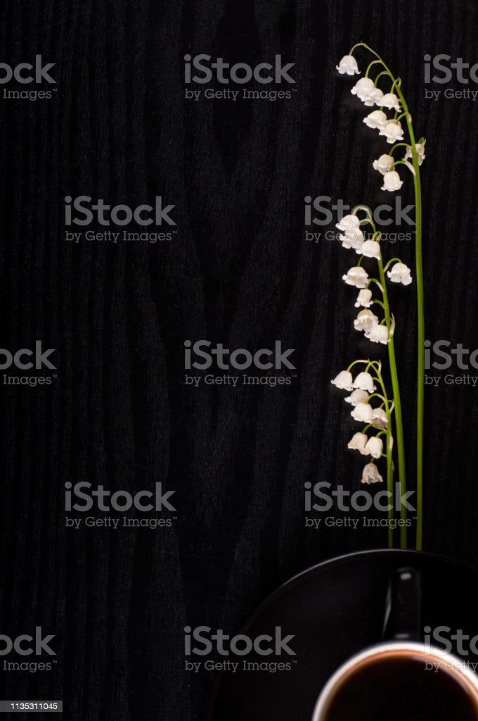 Lilies of the valley and black coffee on a black wooden background,...