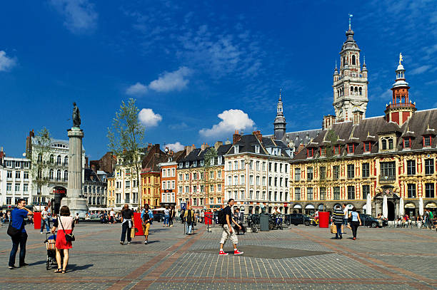 Lille Grand Place Lille, France - August 29, 2013: Lille Grand Place showing the Chamber of Commerce tower and the Vieille Borse with tourists walking across the main square and some traffic in the mid ground. hauts de france stock pictures, royalty-free photos & images