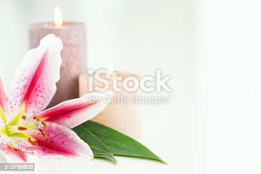 Fragrant pink lily flower and scented lighted candles on white background.