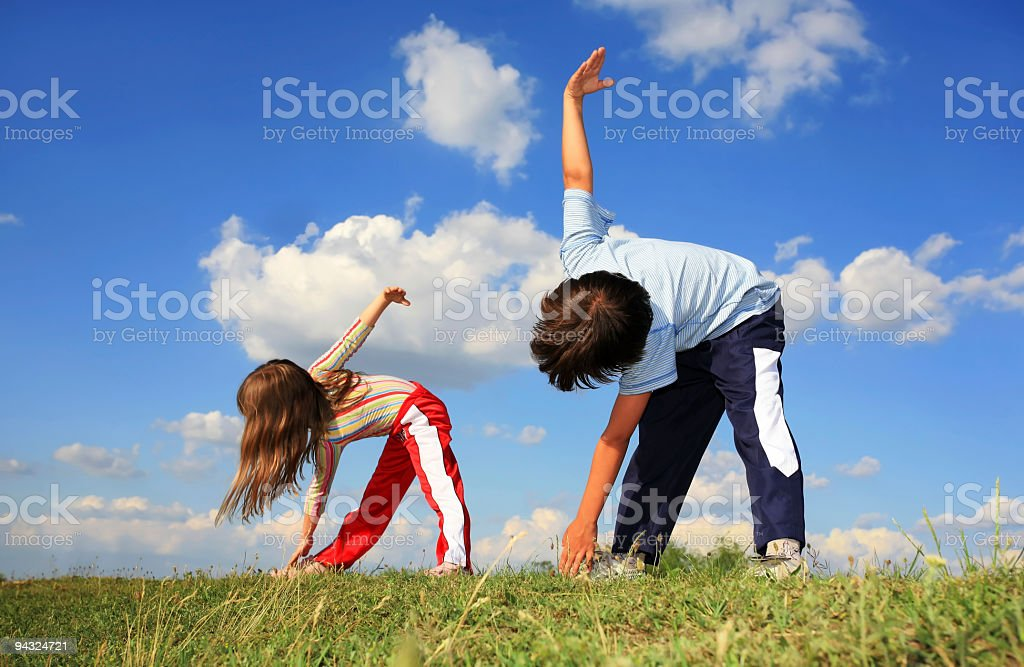 Lilttle Girl and boy exercising on meadow stock photo