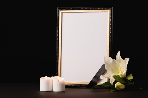 lily, candle and mirror with ribbon on black background, funeral concept