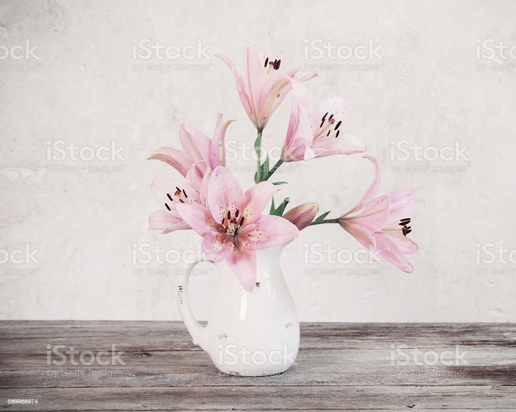 lily in vase on background old white wall stock photo