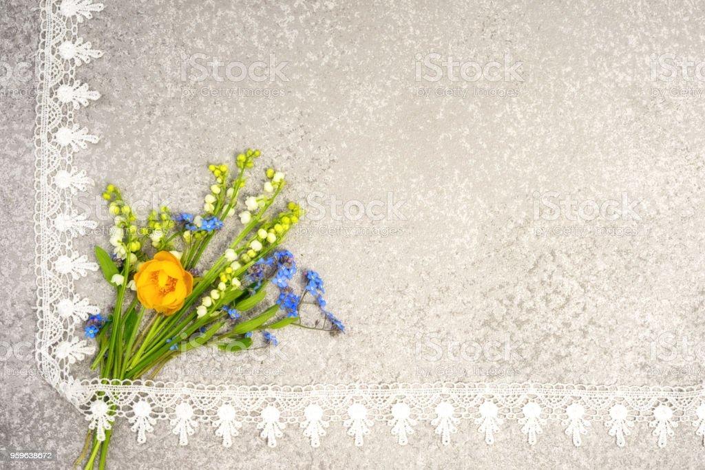 lirio de los valles, pensamientos y ramo de flores de globo en un fondo de plata en el marco de encaje de esquina con espacio de copia de su texto de felicitación. - Foto de stock de Amor libre de derechos