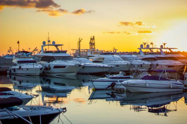 limassol, zypern, 12.28, 2018: limassol marina von yachten über showboote bis hin zu fischerbooten, der malerische yachthafen bei sonnenaufgang ist ruhig unter dem goldenen himmel, bevor der tag beginnt. - hochzeitsreise zypern stock-fotos und bilder