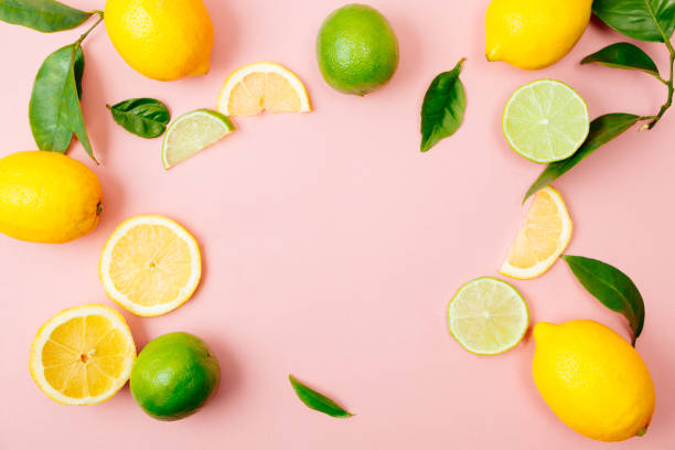 lime and lemon frame on pink background - composition stock pictures, royalty-free photos & images