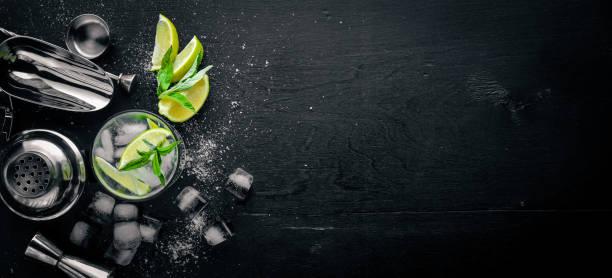 Limão e menta, cocktail, com gelo, numa superfície de madeira preta. Vista superior. Espaço livre. - foto de acervo