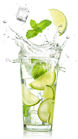 lime and mint falling into a cocktail splashing on white background