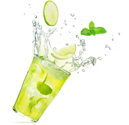 lime and mint falling into a splashing cocktail