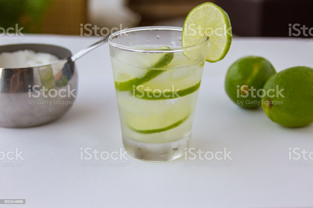 Glass, water, ice cube, slice of limes, two limes, sugar bowl. Copy...