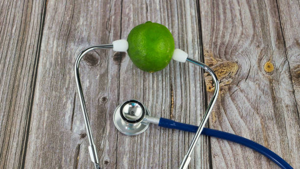 lime fruit on a wooden table with a stethoscope stock photo