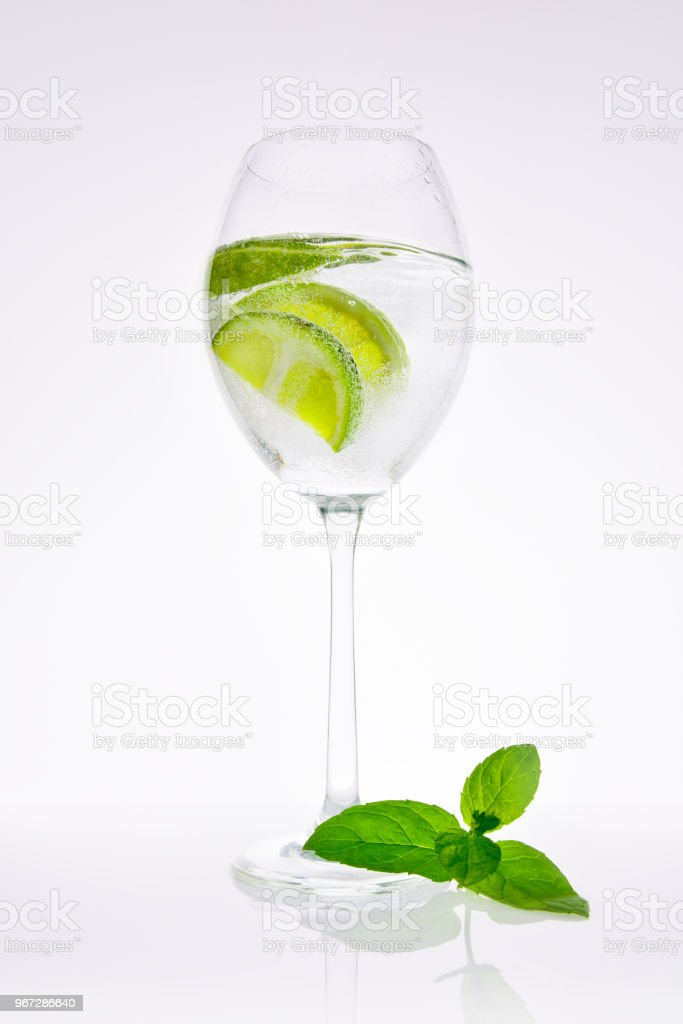 Lime in carbonated water with a mint leaf. stock photo