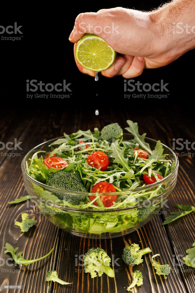 Lime juice is squeezed into a dish with salad stock photo