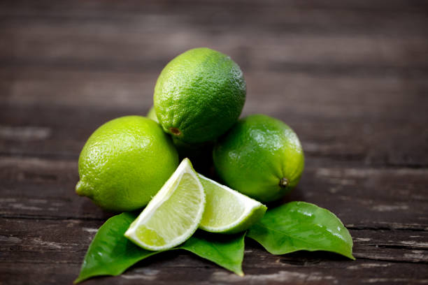 lime juice with lime slices on wooden table stock photo