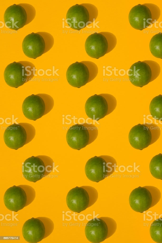 Lime pattern on yellow background. Minimal flat lay concept royalty-free stock photo