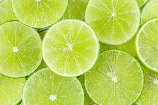 lime fresh green lime sliced background lime stock pictures, royalty-free photos & images