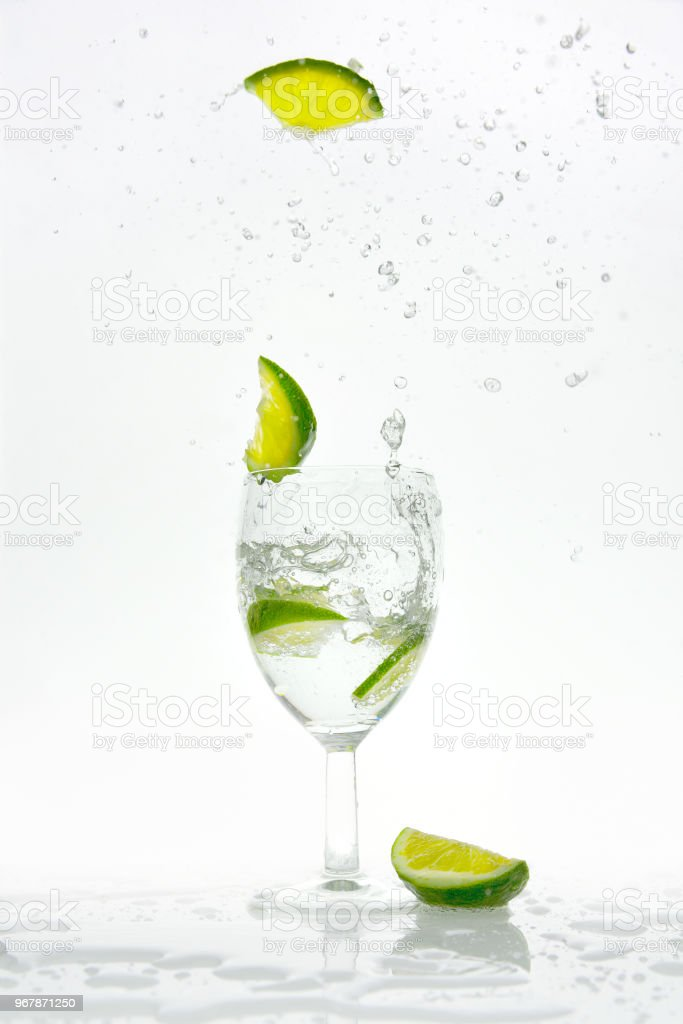 Lime pops from a glass with sparkling water stock photo