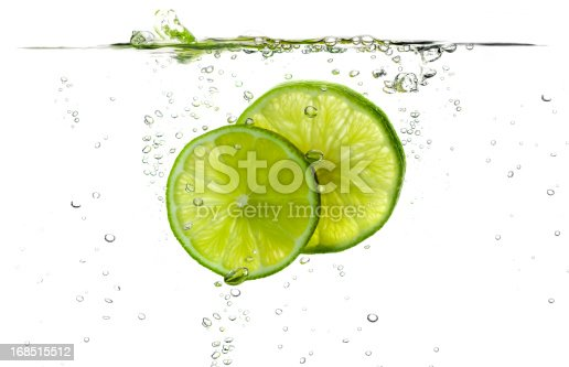 Lime splash slices falling in water.