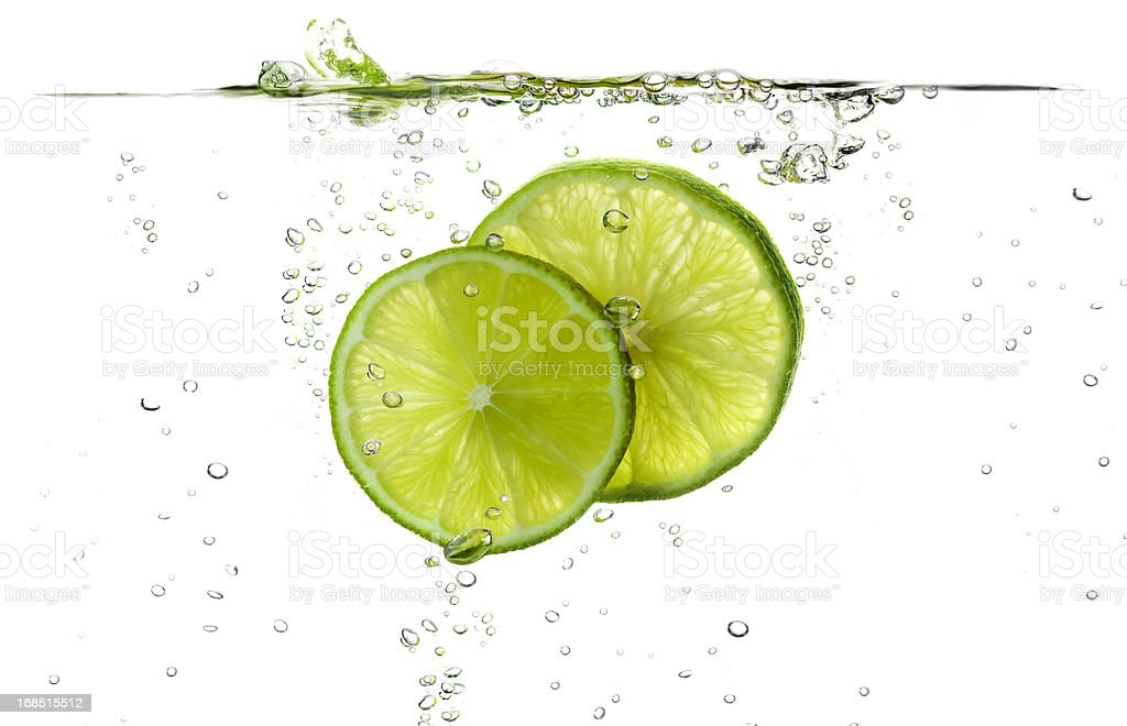 Lime slices splashing in fresh water stock photo