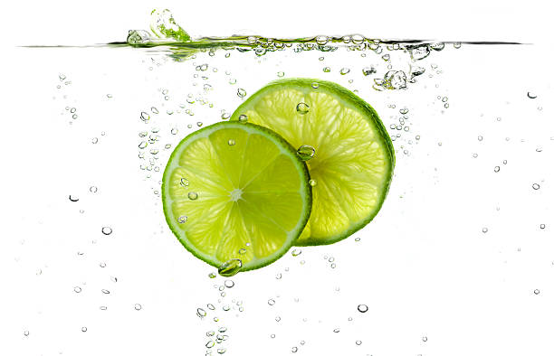 Lime slices splashing in fresh water Lime splash slices falling in water. lemon fruit stock pictures, royalty-free photos & images