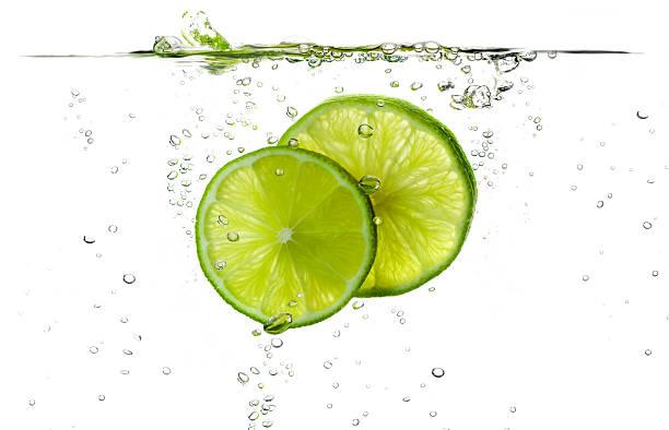 Lime slices splashing in fresh water stock photo