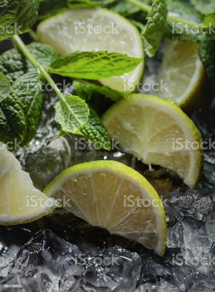 Lime slices with ice and mint on dark background. royalty-free stock photo