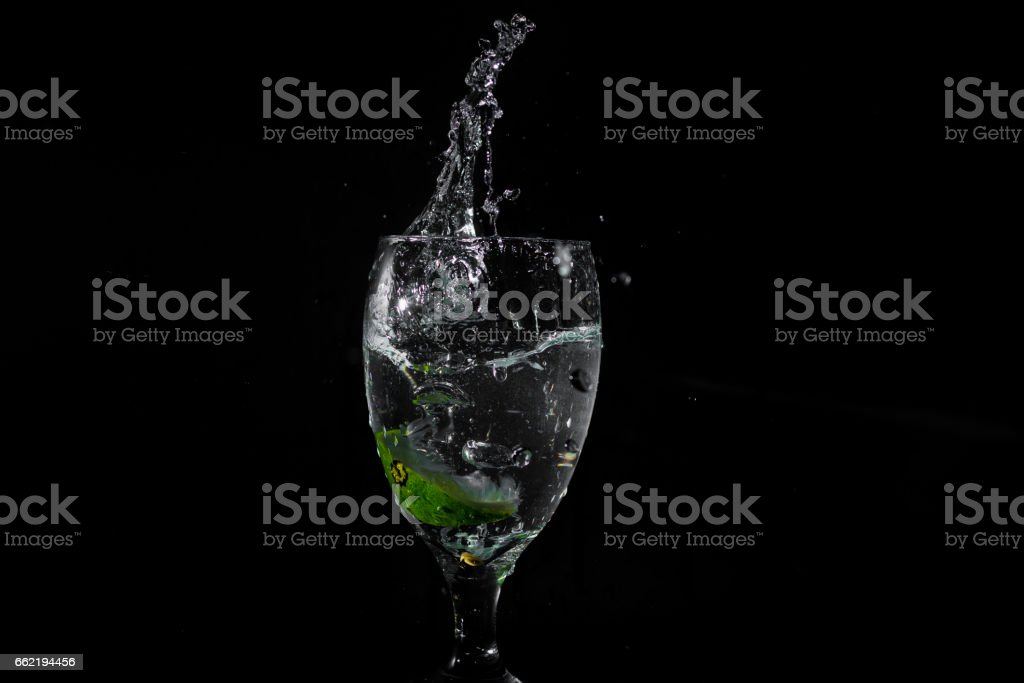A lime splashing into a glass of water stock photo