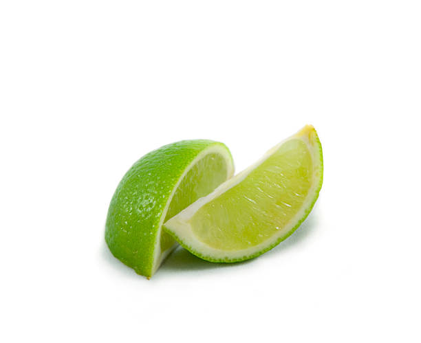 Lime wedges on white  lime stock pictures, royalty-free photos & images