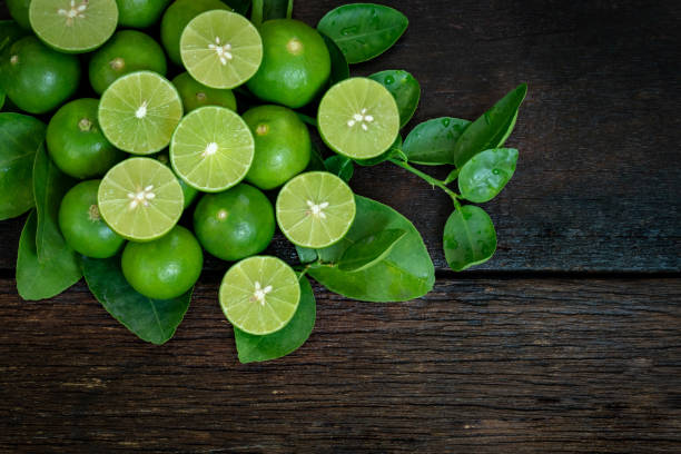 Limes on wooden background lime and limes slice on wooden table lime stock pictures, royalty-free photos & images