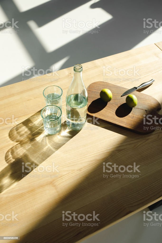 limes on wooden board and water in glasses and bottle on wooden table stock photo