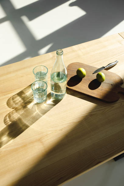 cales en tablero de madera y el agua en vasos y una botella en la mesa de madera - vitamina a fotografías e imágenes de stock