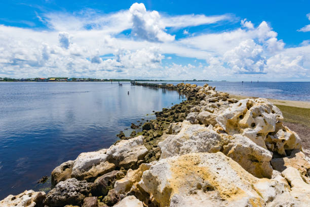 Limestone Seawall Protects a Florida Bay A stone jetty in the Gulf of Mexico protects a harbor entrance. groyne stock pictures, royalty-free photos & images