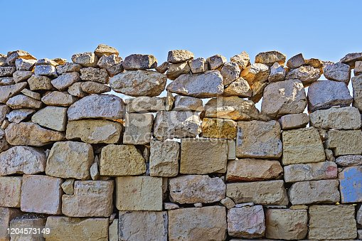 Limestone wall of brickwork with cracked boulders against blue sky background. Natural build texture with copy spac