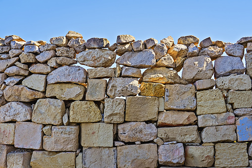Limestone wall of brickwork with cracked boulders against blue sky