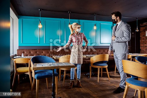 A limited number of guests in the restaurant at the time of the coronavirus. A female hostess and waitress point to a empty table for a man in a business suit. Covid social distance