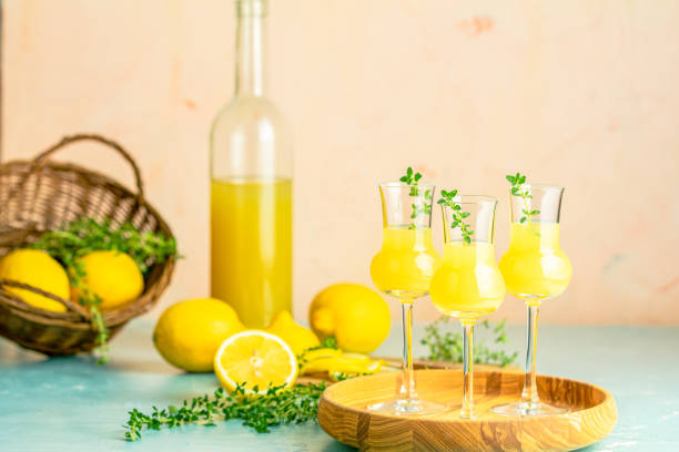 Limoncello with thyme in grappas wineglass with water drops on light concrete table. Artistic still life on light background with sunny light. stock photo