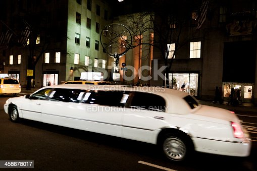 New York, United States - January 14, 2012: White limousine driving in Fifth Avenue in front of the Rockefeller Center in Manhattan New York at night