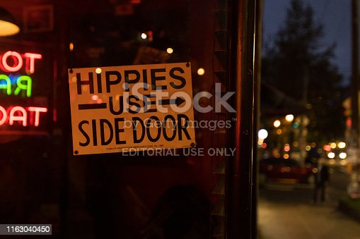 Seattle, USA - Apr 19, 2019: The famous hippies use side door sign at the iconic Lindas Bar on Capitol Hill early in the evening. Lindas is a cowboy themed bar that has been open for 25 years. It's also known as the last known public place Kurt Cobain was seen alive.
