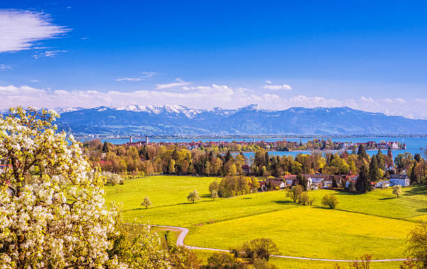 Lindau and Austrian Alps at Lake Constance (Bodensee) at spring Elevated view on the beautiful bavarian island town of Lindau at Lake Constance (Bodensee), with blooming apple trees and the snow-covered Austrian alps and town of Bregenz at the distance. Bodensee stock pictures, royalty-free photos & images