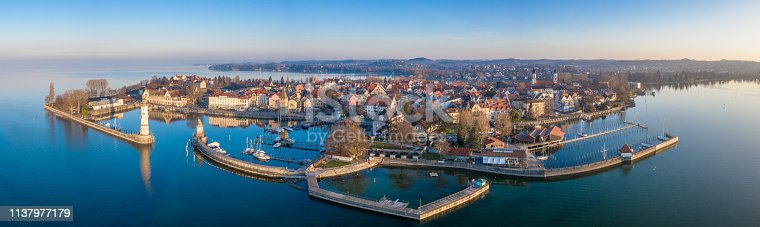 Aerial Drone Panorama at sunrise towards the Lindau Island, Old Town and Waterfront Cityscape. Lindau Harbor Bodensee Entrance with the famous old Lighthouse (left) and Bavarian Lion Sculpture from the year 1856. Lindau Waterfront Promenade with Mangenturm, Restaurants and Hotels in the Background. Stiched XXXL Panorama. Lindau, Bodensee, Bavaria, Germany.