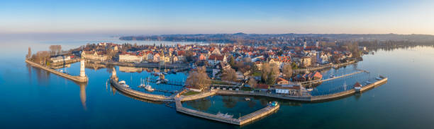 Lindau at Sunrise Aerial Panorama Bodensee Germany Aerial Drone Panorama at sunrise towards the Lindau Island, Old Town and Waterfront Cityscape. Lindau Harbor Bodensee Entrance with the famous old Lighthouse (left) and Bavarian Lion Sculpture from the year 1856. Lindau Waterfront Promenade with Mangenturm, Restaurants and Hotels in the Background. Stiched XXXL Panorama. Lindau, Bodensee, Bavaria, Germany. Bodensee stock pictures, royalty-free photos & images
