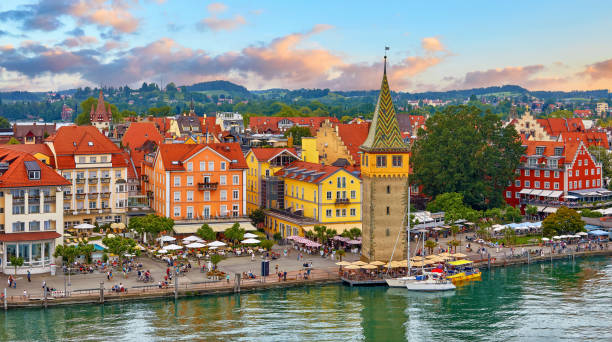 Lindau, Germany. Antique town in Bavaria at Bodensee Lake Lindau, Germany. Antique Bavarian town in Bavaria at coastline of Lake Constance (Bodensee). Habour along embankment with traditional houses and tower. Sunset evening landscape. Bodensee stock pictures, royalty-free photos & images