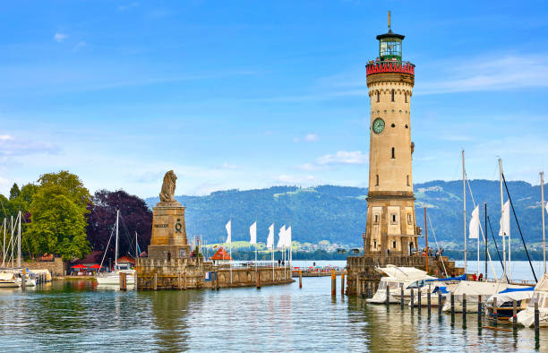 Lindau, Germany. Old lighthouse with clock in the bay Lindau, Germany. Old lighthouse with clock in bay. Antique bavarian town at Lake Constance (Bodensee). Monument with statue of lion at entrance to port, yachts by piers. Summer landscape blue sky. Bodensee stock pictures, royalty-free photos & images