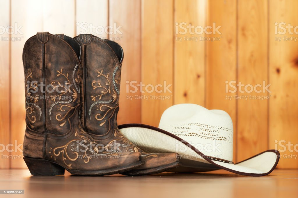 cowgirl embroidered boots and white hat on wooden background - text...