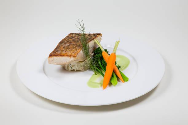 linha de peixe com cenouras e brócolis em um prato branco sobre um fundo branco - fine dining - fotografias e filmes do acervo