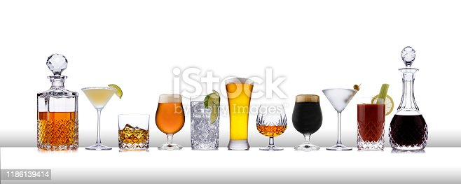A line of aclcoholic drinks from whisky to lager, in a line, on a white bar like surface, with a white background