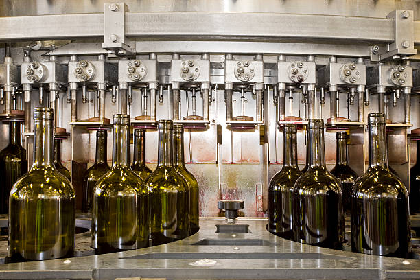 a line of bottles getting corks inserted by a machine - bottling plant stock photos and pictures